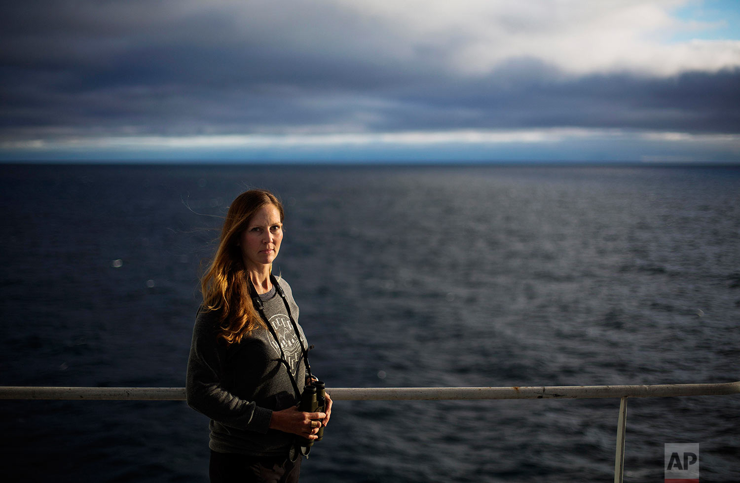 """Field biologist Paula von Weller, 45, of Portland, Ore., stands for a portrait aboard the Finnish icebreaker MSV Nordica as it sails in the North Pacific Ocean toward the Bering Strait, Tuesday, July 11, 2017. """"Few people in the world get to sail the Northwest Passage,"""" said von Weller, who will be marking her second passage after traveling through with another Finnish icebreaker in 2015. She is observing wildlife in the Arctic and hopes this time to see the elusive narwhal, the unicorn of the sea. """"I've been fascinated with the Arctic. It is very special to me. I think it's just this mythical place."""" (AP Photo/David Goldman)"""