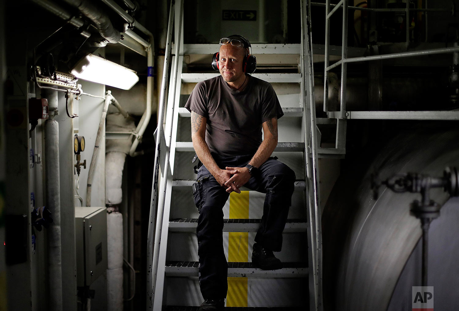 """First engineer Kristian Autio, 44, sits for a portrait in the engine room of the Finnish icebreaker MSV Nordica as it sails in the North Pacific Ocean toward the Bering Strait, Sunday, July 9, 2017. Autio has worked aboard Finnish icebreakers since 2002 and this will be his first time crossing the Arctic's Northwest Passage. Finland has a long history of building icebreakers and has built 60 percent of the world's fleet. """"We take care of the ship as if it's our own,"""" said Autio. """"We [Finns] are very proud of our icebreakers."""" (AP Photo/David Goldman)"""
