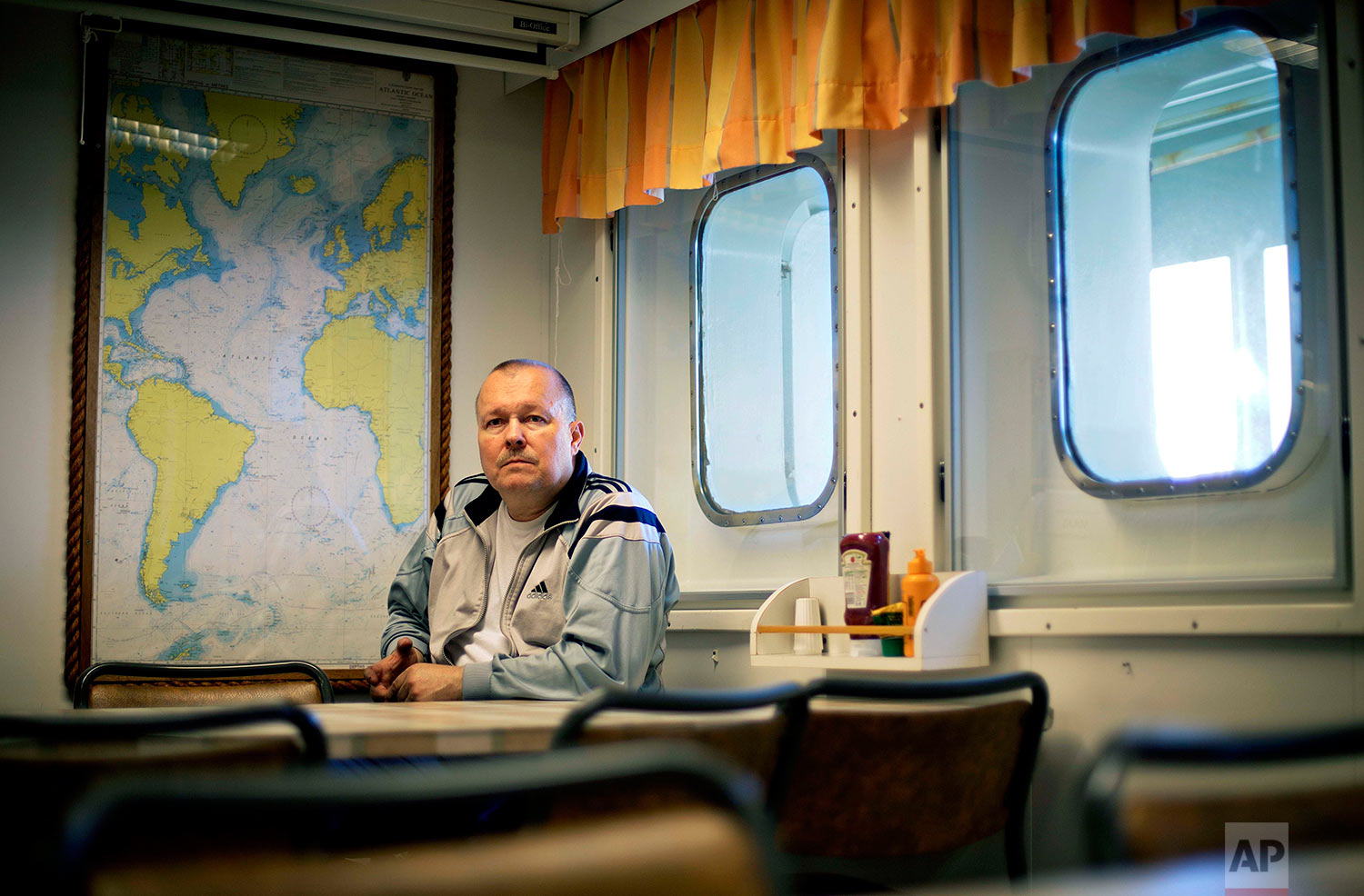 "Engine repairman Jari Jarvinen, 58, sits for a portrait in the mess hall after finishing a night shift aboard the Finnish icebreaker MSV Nordica as it sails in the North Pacific Ocean toward the Bering Strait, Tuesday, July 11, 2017. Jarvinen started working on boats over 30 years ago. ""I've been there before. For me it's normal work,"" said Jarvinen of the Northwest Passage. ""I like it though. Not everyday is the same. You look outside the window and it's always a different place."" (AP Photo/David Goldman)"