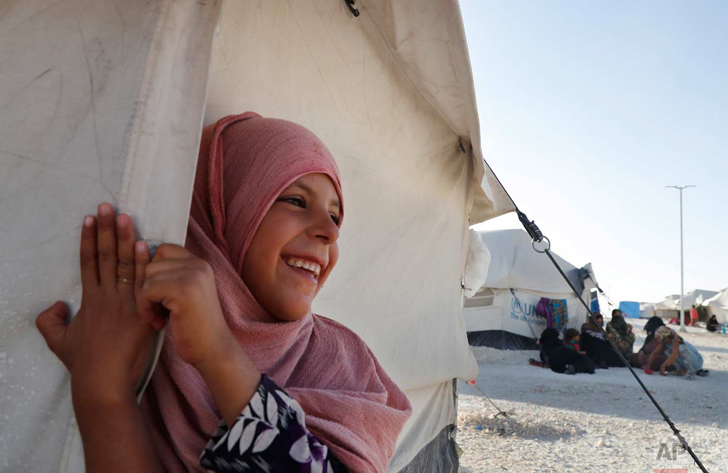 A girl who fled with her family from the battle between U.S.-backed Syrian Democratic Forces and the Islamic State militants from Raqqa city, stands outside her tent at a refugee camp, in Ain Issa town, northeast Syria, Wednesday, July 19, 2017. (AP Photo/Hussein Malla)