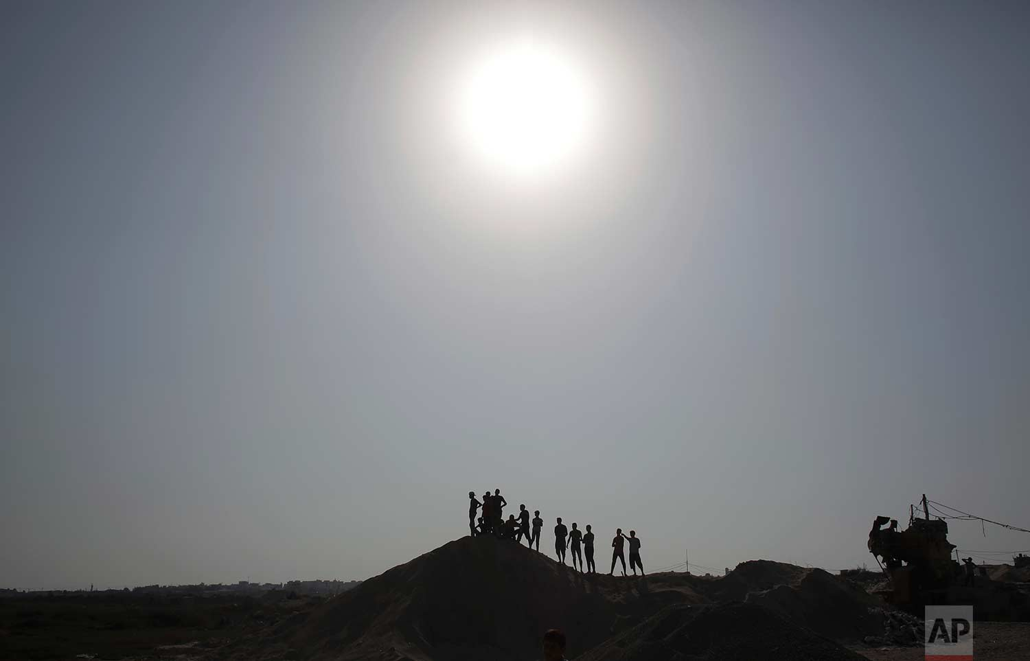 Palestinian protesters stand atop a sandy hill during clashes with Israeli soldiers on the Israeli border with Gaza, Friday, July 21, 2017. (AP Photo/ Khalil Hamra)