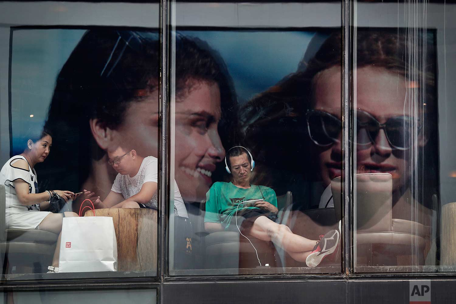 With a fashion advertisement billboard reflected in the windows, people spend time in a cafe at a shopping mall in Beijing, on Monday, July 17, 2017. (AP Photo/Andy Wong)