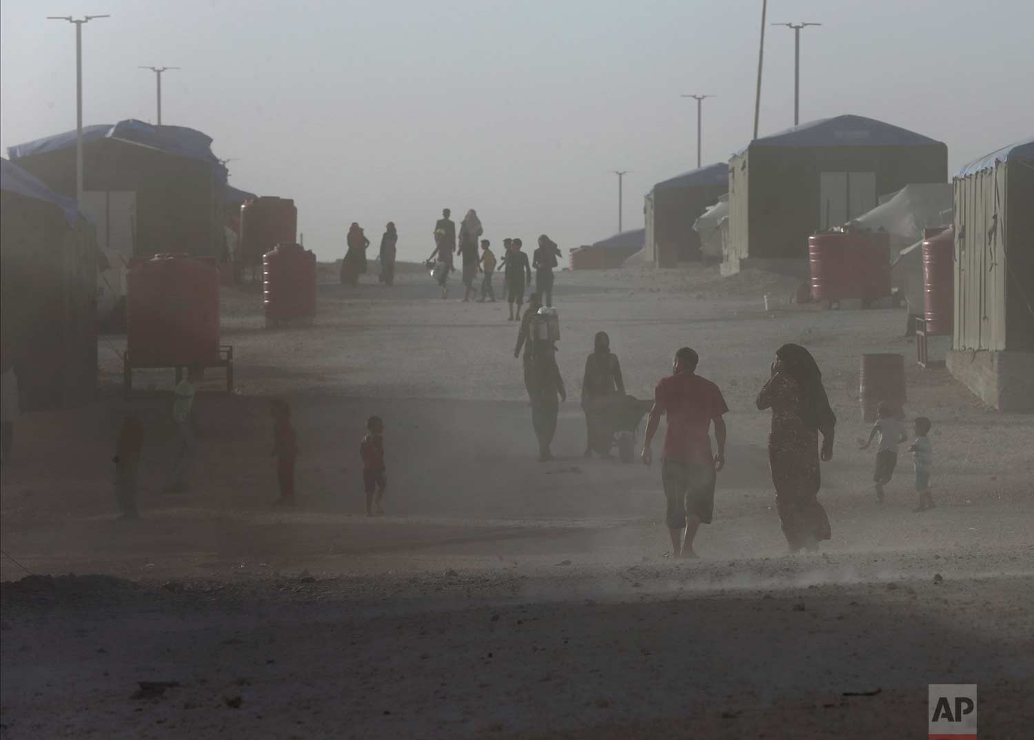 People who fled the battles between U.S.-backed Syrian Democratic Forces and the Islamic State militants from Raqqa, walk in the dust at a refugee camp, in Ain Issa, northeast Syria on Wednesday, July 19, 2017. (AP Photo/Hussein Malla)