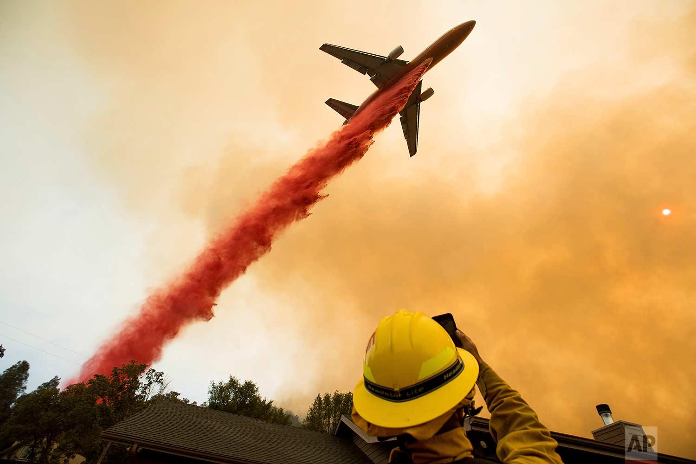 An air tanker drops fire retardant while battling a wildfire near Mariposa, Calif., Wednesday, July 19, 2017. (AP Photo/Noah Berger)