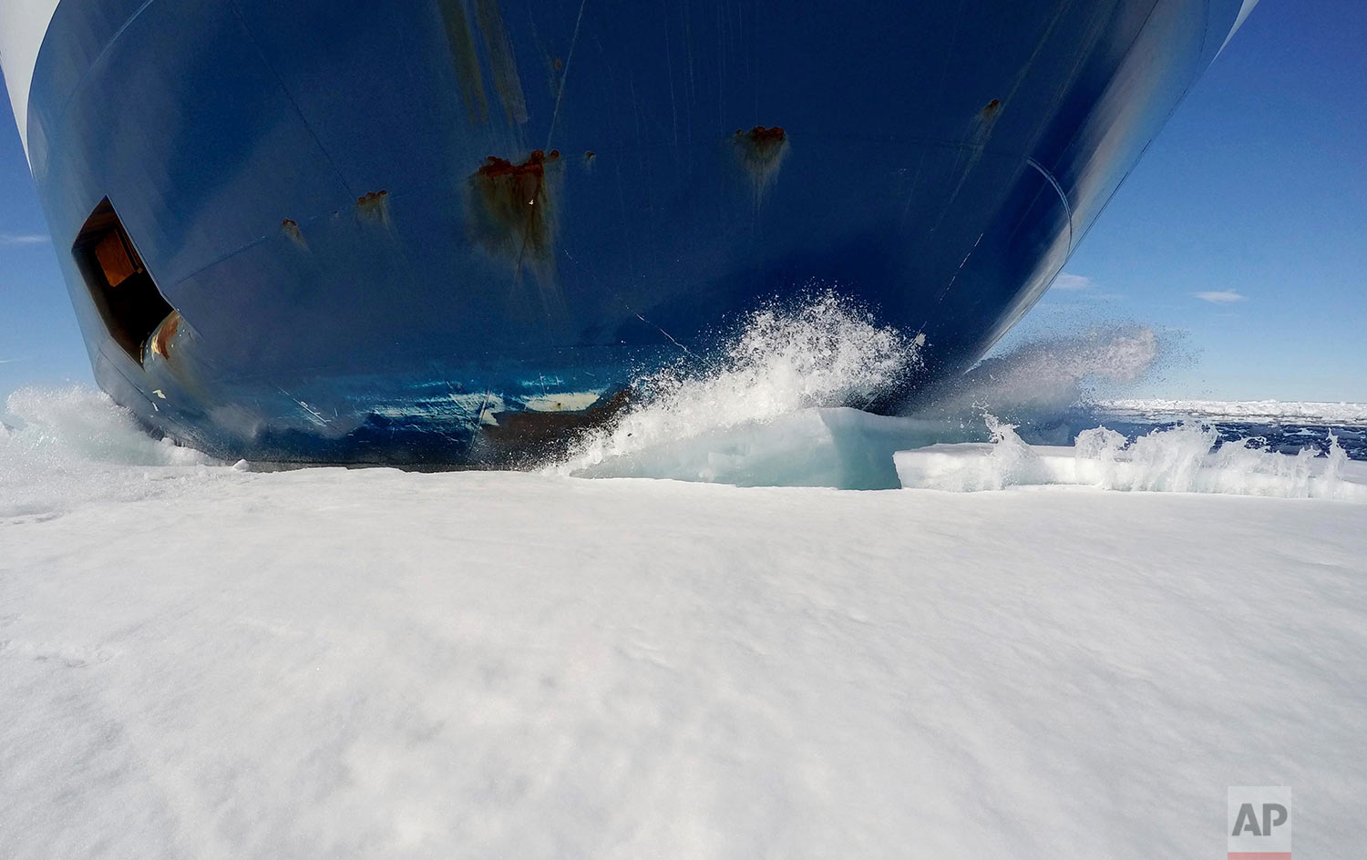 The bow of the Finnish icebreaker MSV Nordica drives through sea ice as it sails the Victoria Strait while traversing the Arctic's Northwest Passage, Friday, July 21, 2017. The MSV Nordica is equipped with several heavy-duty engines and a hardened bow and hull that allow it either to drive through thin layers of ice or to crush thicker sheets by rising onto the ice with the help of its rounded hull. The ship's massive weight breaks the ice from above. (AP Photo/David Goldman)