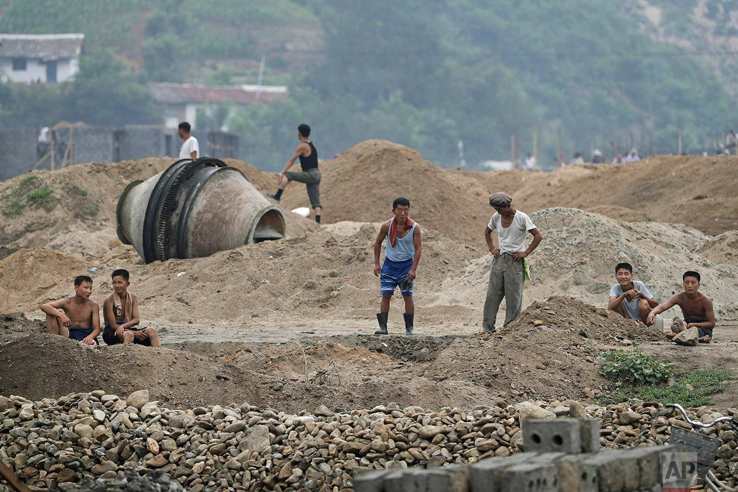 In this Friday, July 21, 2017, photo, men and boys rest at a construction site on the outskirts of Hamhung, North Korea's second-largest city, where construction workers unearthed a rusted but still potentially deadly mortar round in February. (AP Photo/Wong Maye-E)