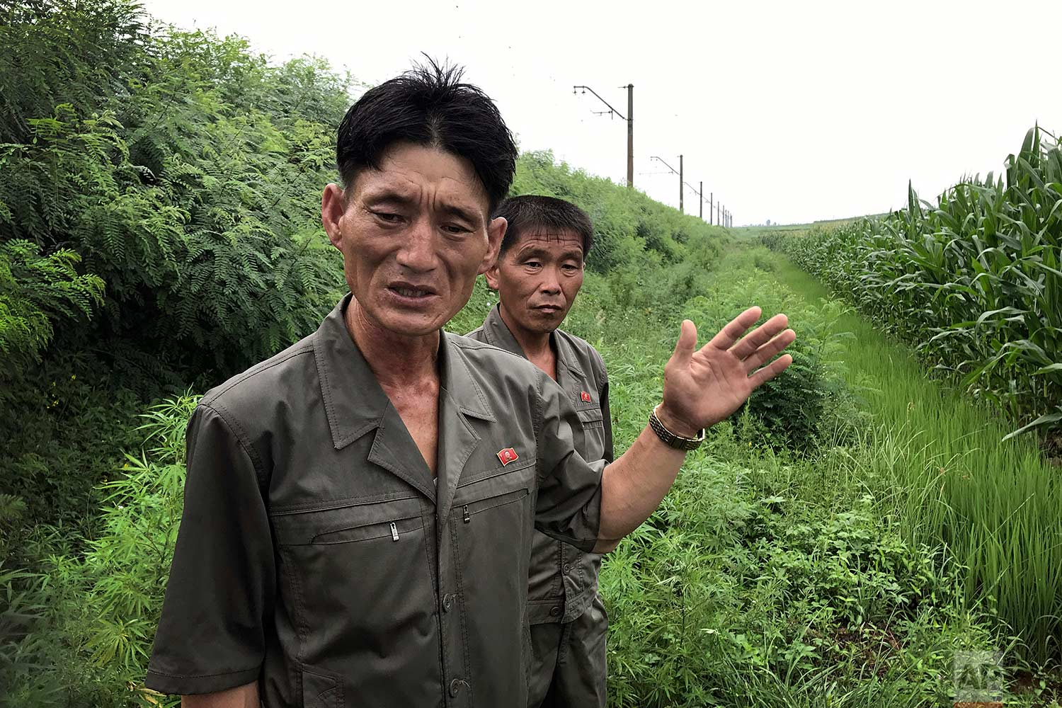 In this Friday, July 21, 2017, photo, Yom Hak Chol, 44, manager of the 4th work team of the Pohang cooperative farm, left, and Paek Song Guk, 44, who found an unexploded bomb near the railway which runs through Hamhung from Pyongyang to the northeastern port of Chongjin, speak to The Associated Press in Hamju county, North Korea. (AP Photo/Wong Maye-E)