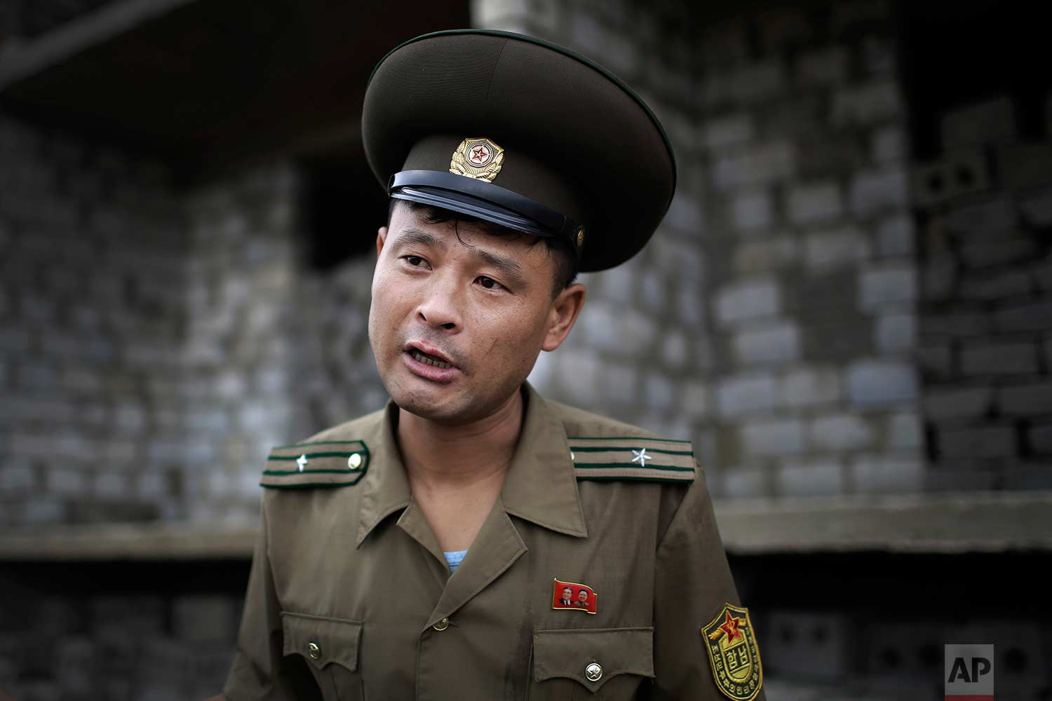 In this Friday, July 21, 2017, photo, Maj. Jong Il Hyon, 44, a member of a bomb squad for South Hamgyong, speaks to The Associated Press at a construction site on the outskirts of Hamhung, North Korea's second-largest city, where workers unearthed a rusted but still potentially deadly mortar round in February. (AP Photo/Wong Maye-E)