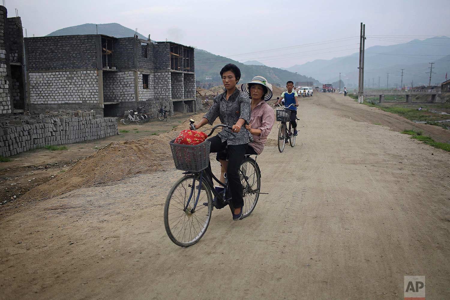 In this Friday, July 21, 2017, photo, women cycle past a construction site on the outskirts of Hamhung, North Korea's second-largest city, where construction workers unearthed a rusted but still potentially deadly mortar round in February. (AP Photo/Wong Maye-E)
