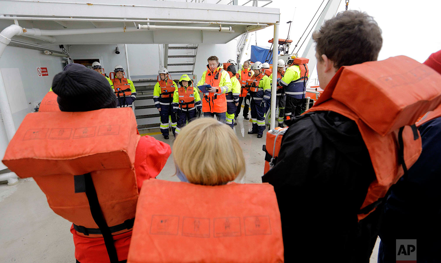 Second officer Ilkka Alhoke, center, conducts a safety drill aboard the Finnish icebreaker MSV Nordica as it sails through Barrow Strait while traversing the Northwest Passage through the Canadian Arctic Archipelago, Sunday, July 23, 2017. (AP Photo/David Goldman)