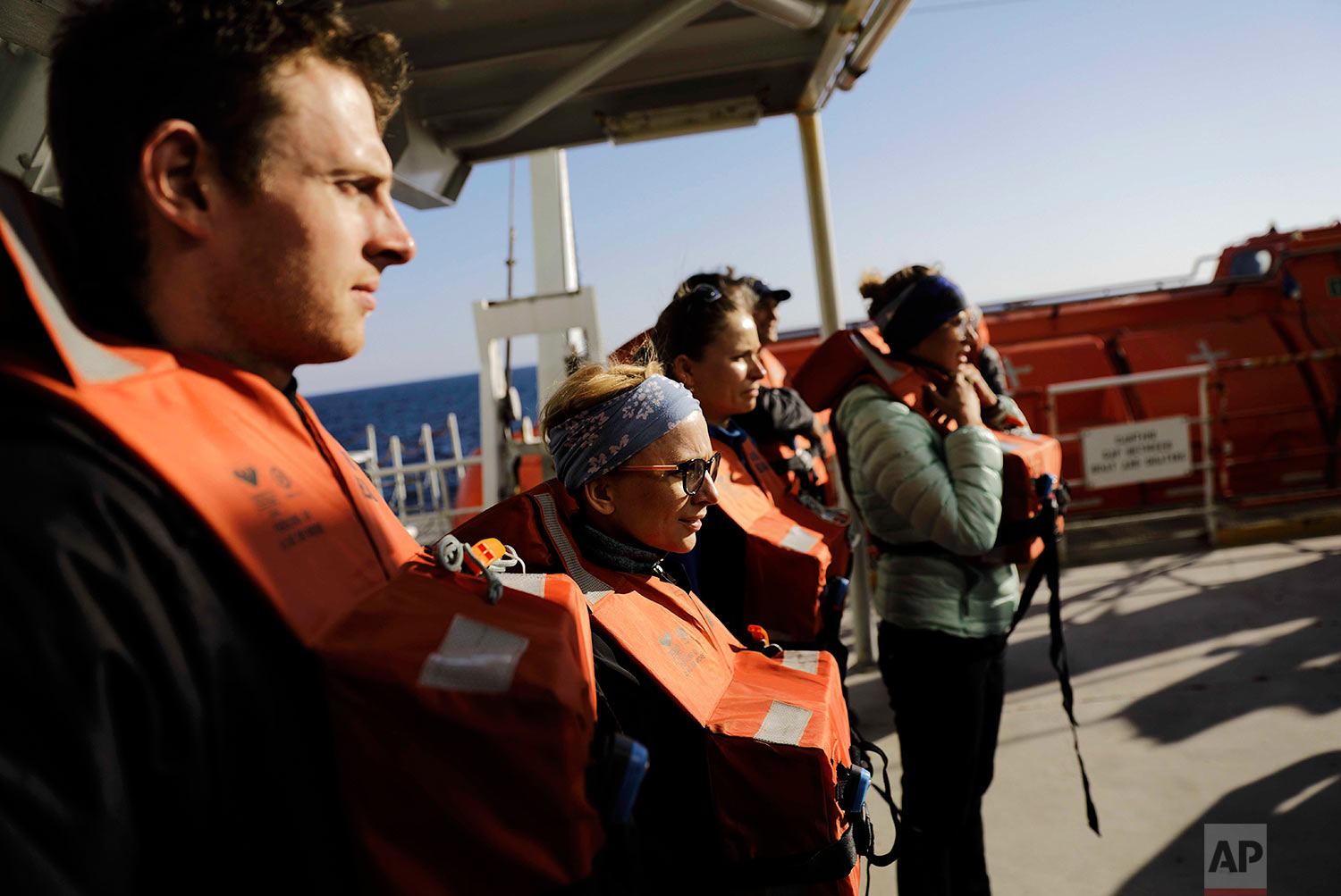 Researchers Scott Joblin, from left, and Ilona Mettiainen, wear life vests during a safety drill with fellow personnel aboard the Finnish icebreaker MSV Nordica as it sails the North Pacific Ocean to traverse the Arctic's Northwest Passage, Thursday, July 6, 2017. (AP Photo/David Goldman)