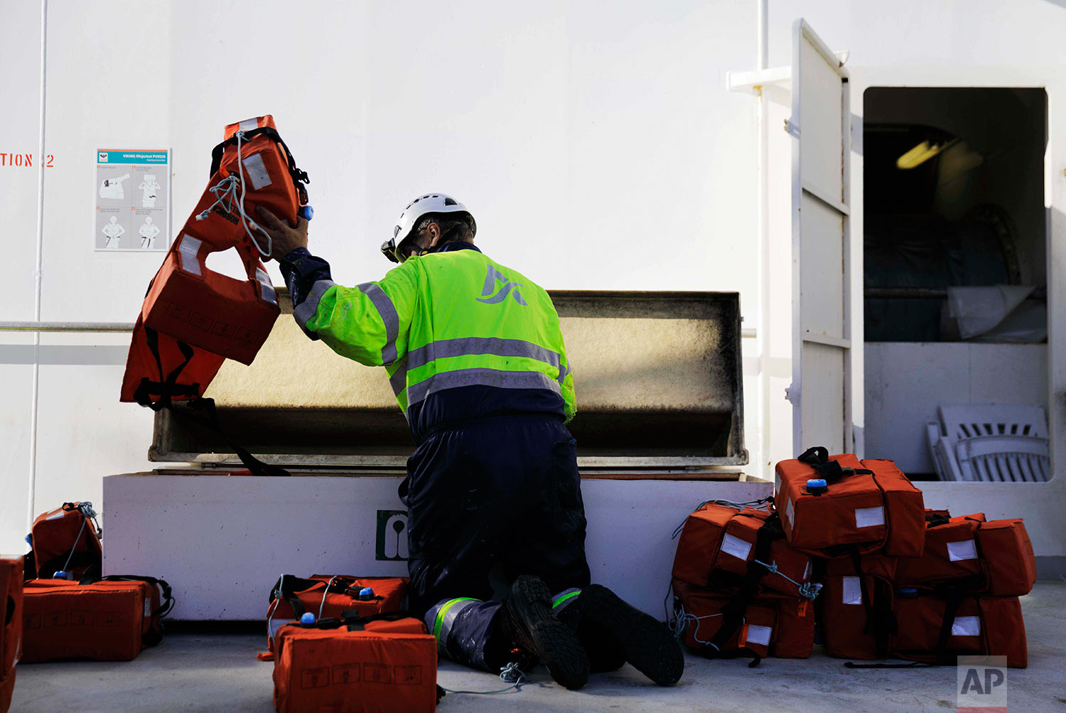 Able seaman Auvo Sinkkonen puts away life vests after a safety drill aboard the Finnish icebreaker MSV Nordica as it sails the Northwest Passage through the Canadian Arctic Archipelago, Thursday, July 6, 2017. (AP Photo/David Goldman)