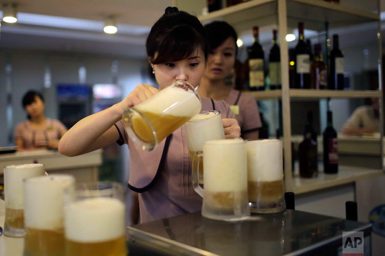 In this Wednesday, July 26, 2017, photo, a waitress pours a new type of Taedonggang beer, the eighth in its line of specialty brews, made of wheat and hops at the Taedonggang Brewery in Pyongyang, North Korea. (AP Photo/Wong Maye-E)