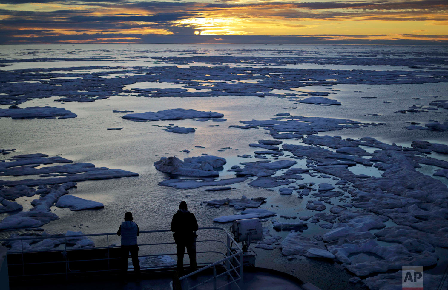 Researchers look out from the Finnish icebreaker MSV Nordica as the sun sets over sea ice floating on the Victoria Strait along the Northwest Passage in the Canadian Arctic Archipelago, Friday, July 21, 2017. Sea ice plays an important role in the global climate system by cooling the surrounding water and air. It helps maintain ocean and atmospheric currents that affect weather which is characteristic for certain parts of the world, such as the comparatively mild temperatures found in western Europe. (AP Photo/David Goldman)