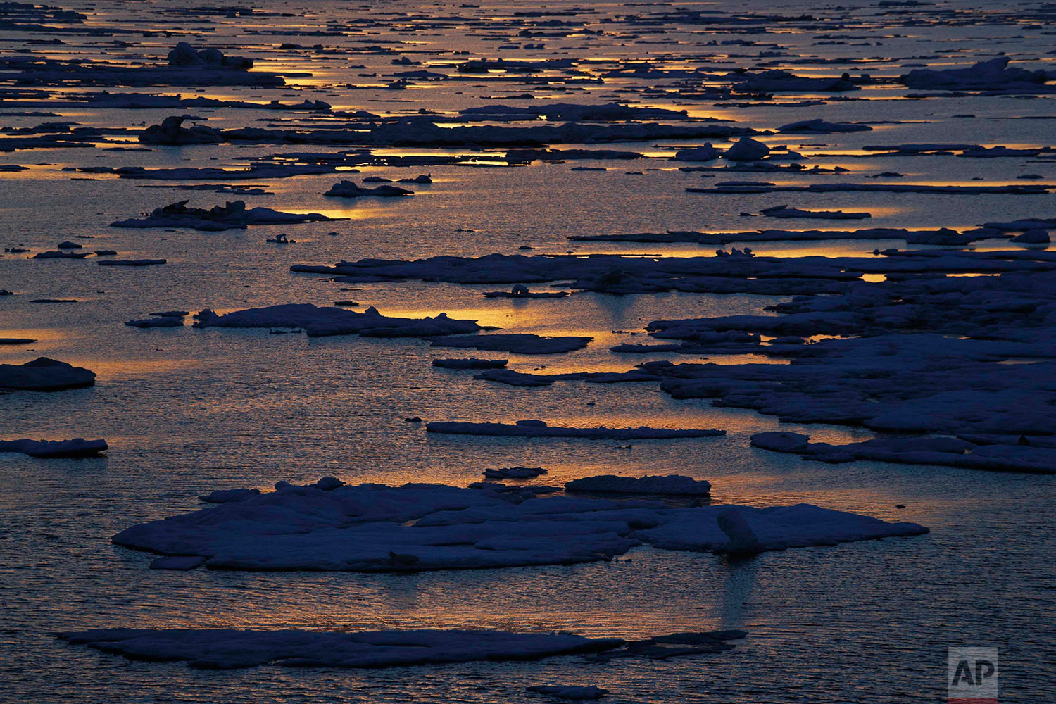 The sun sets over sea ice floating on the Victoria Strait along the Northwest Passage in the Canadian Arctic Archipelago, Friday, July 21, 2017. Sea ice forms when the top layer of water reaches freezing point, usually around the start of October. As temperatures continue to fall this first-year ice grows downward until it is several feet thick. If the ice survives the following summer melt it becomes second-year ice. Another cycle and it becomes multi-year ice _ which is the toughest kind. (AP Photo/David Goldman)