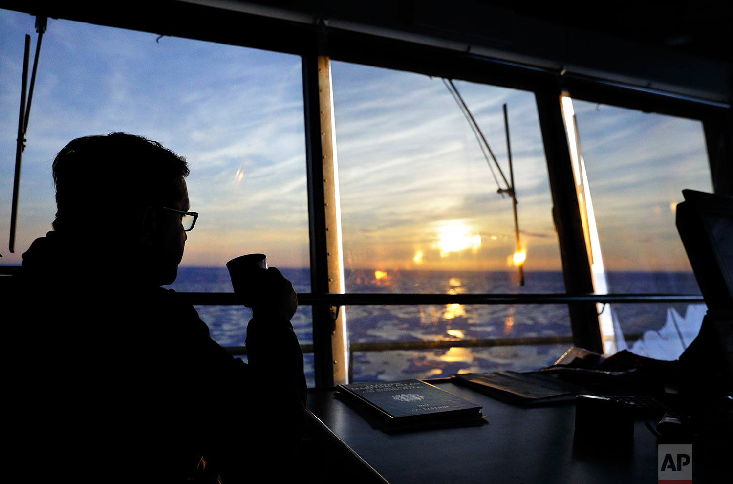 "Sunlight is cast over the sea ice at midnight as Master Mariner Jyri Viljanen, captain of the Finnish icebreaker MSV Nordica, sips a cappuccino while overseeing the navigation of the Northwest Passage through the Victoria Strait in the Canadian Arctic Archipelago, early Saturday, July 22, 2017. Viljanen has been going to sea for 39 years and is making his first transit through the Arctic's Northwest Passage. ""It's once a lifetime,"" said Viljanen of the opportunity. (AP Photo/David Goldman)"