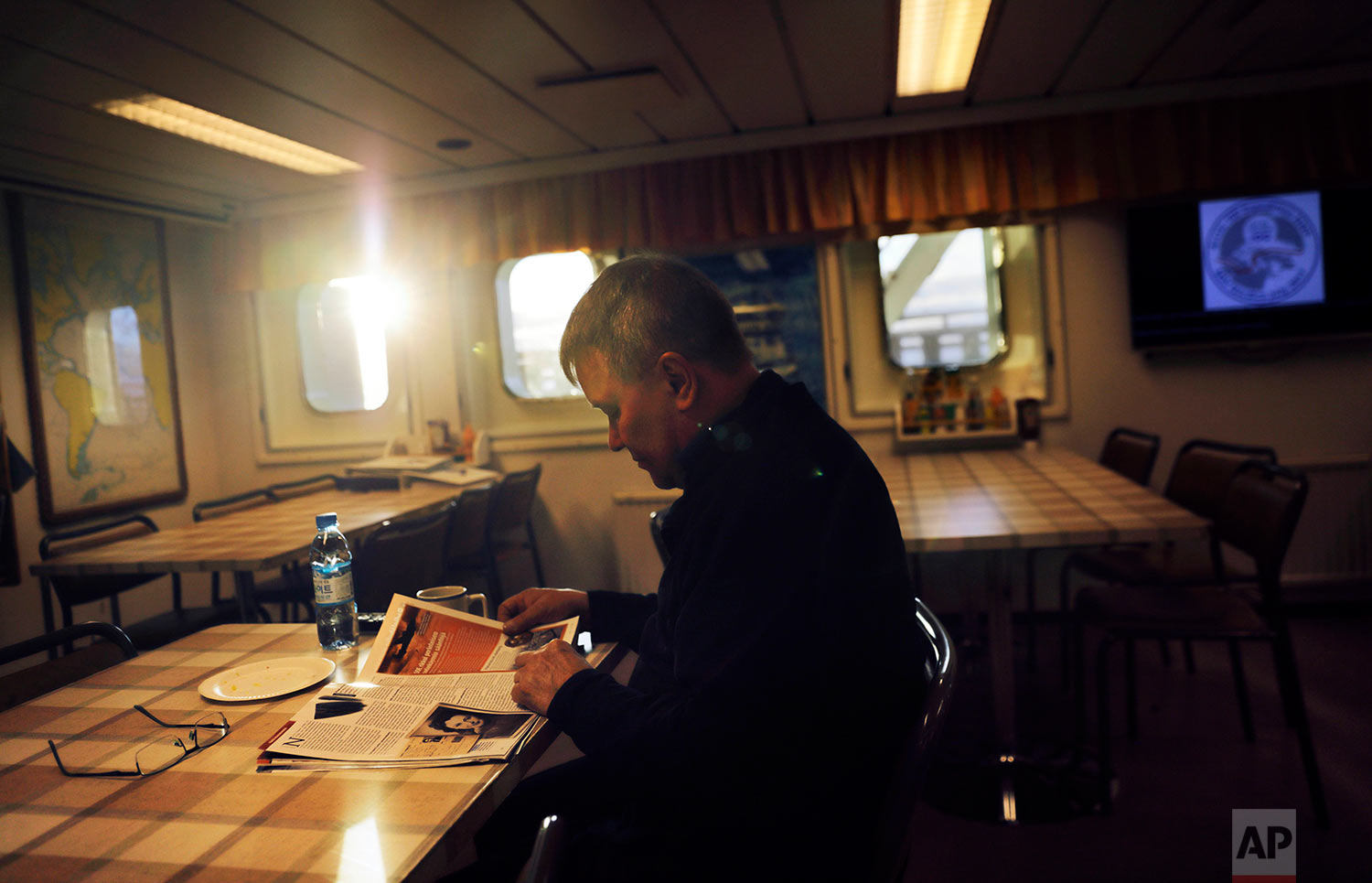 "The sun shines through the window of the mess hall at midnight as first engineer Kari Suni reads a magazine over a cup of coffee before starting his shift in the engine room of the Finnish icebreaker MSV Nordica as it traverses the Northwest Passage through the Canadian Arctic Archipelago, early Monday, July 17, 2017. Suni has worked on icebreakers for 30 years and always starts his shift with a cup of coffee. After all those years, he prefers the overnight shift rather than working during the day. ""It's so quiet and not in a hurry all the time,"" Suni said. ""The dark is good for me."" (AP Photo/David Goldman)"