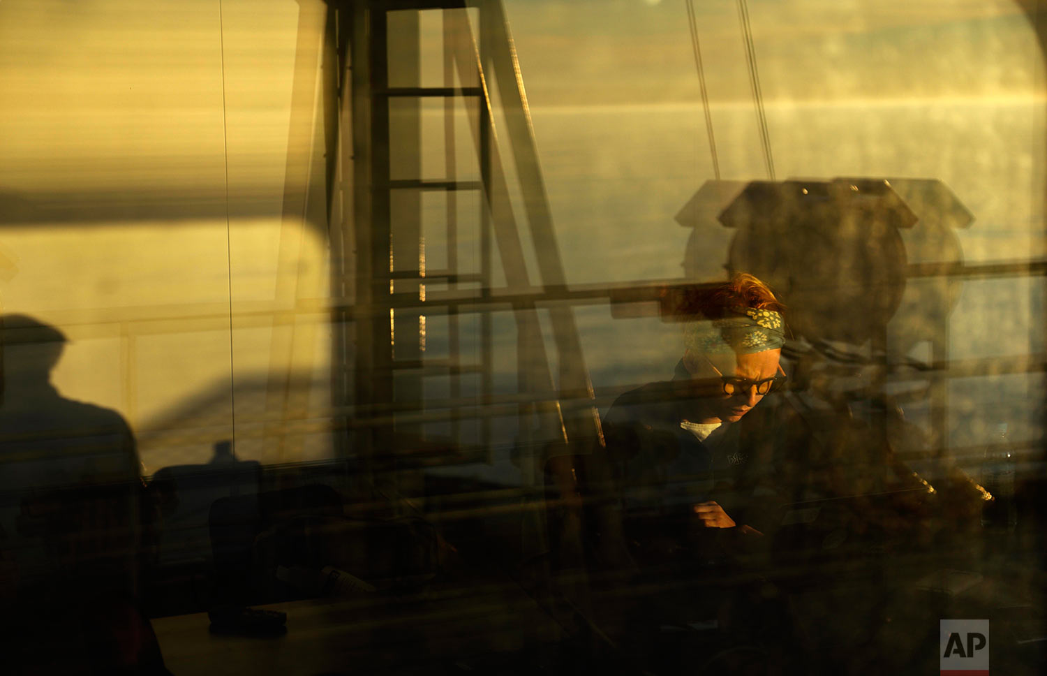 "The sun shines through the window at midnight as researcher Ilona Mettiainen reads in a room overlooking an observation deck on the Finnish icebreaker MSV Nordica as it sails the Bering Sea toward the Canadian Arctic Archipelago to traverse the Northwest Passage, early Friday, July 14, 2017. Mettiainen is working on her doctorate in sociology and is exploring how climate change affects Arctic communities. Mettiainen grew up in Rovanaiemi, Finland, close to the Arctic circle. ""When I was a kid I couldn't really sleep when there was daylight in the evening,"" said Mettiainen. ""I'm used to it now since my childhood so it's a home thing for me. It feels like home."" (AP Photo/David Goldman)"