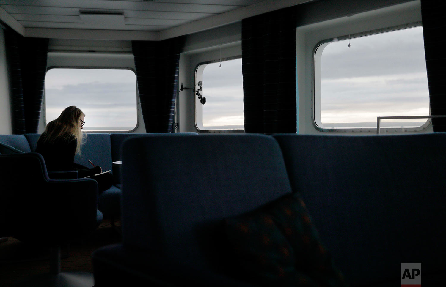 "Daylight lingers behind the clouds at midnight as researcher Tiina Jaaskelainen writes in her diary aboard the Finnish icebreaker MSV Nordica while traversing the Northwest Passage though the Canadian Arctic Archipelago, early Monday, July 24, 2017. ""Midnight is the best time to write your research diary. Especially when the sea gets a bit rough and the rest of the special personnel have gone to sleep,"" said Jaaskelainen who is exploring conflicts between local communities and extractive industries. ""You start seeing things from a different angle and small things become meaningful."" (AP Photo/David Goldman)"