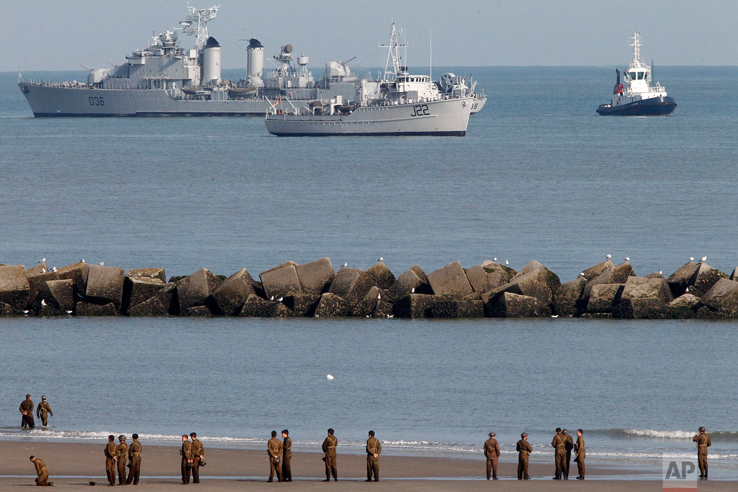 """Actors wait on the beach before filming a scene for the film, """"Dunkirk,"""" in Dunkirk, northern France, Thursday, May 26, 2016. The film, directed by Christopher Nolan, tells the story of the Dunkirk evacuation. (AP Photo/Michel Spingler)"""