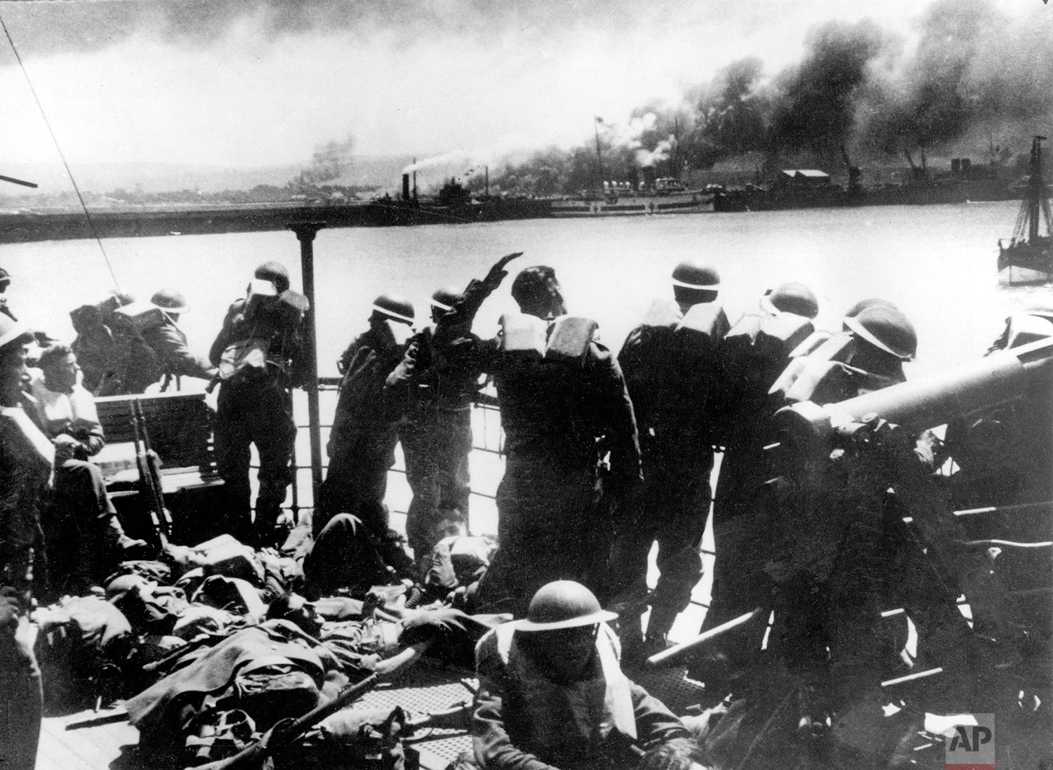 Troops of the British Expeditionary Force view the Nazi bombardment of Dunkirk from a transport after their evacuation from the French coast during World War II. (AP Photo)