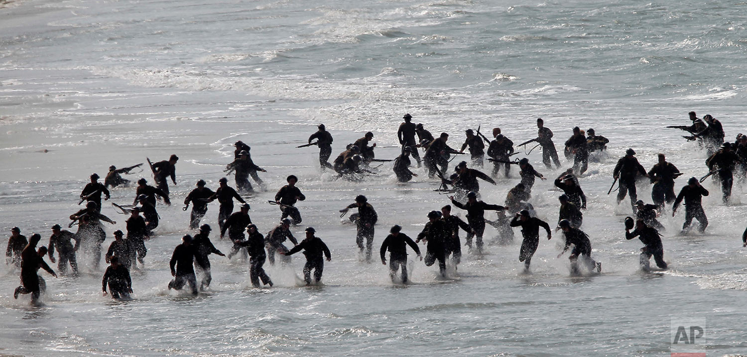 """Actors perform on the beach during filming a scene for the film, """"Dunkirk,"""" in Dunkirk, northern France, Thursday, May 26, 2016. The film, directed by Christopher Nolan, tells the story of the Dunkirk evacuation. (AP Photo/Michel Spingler)"""