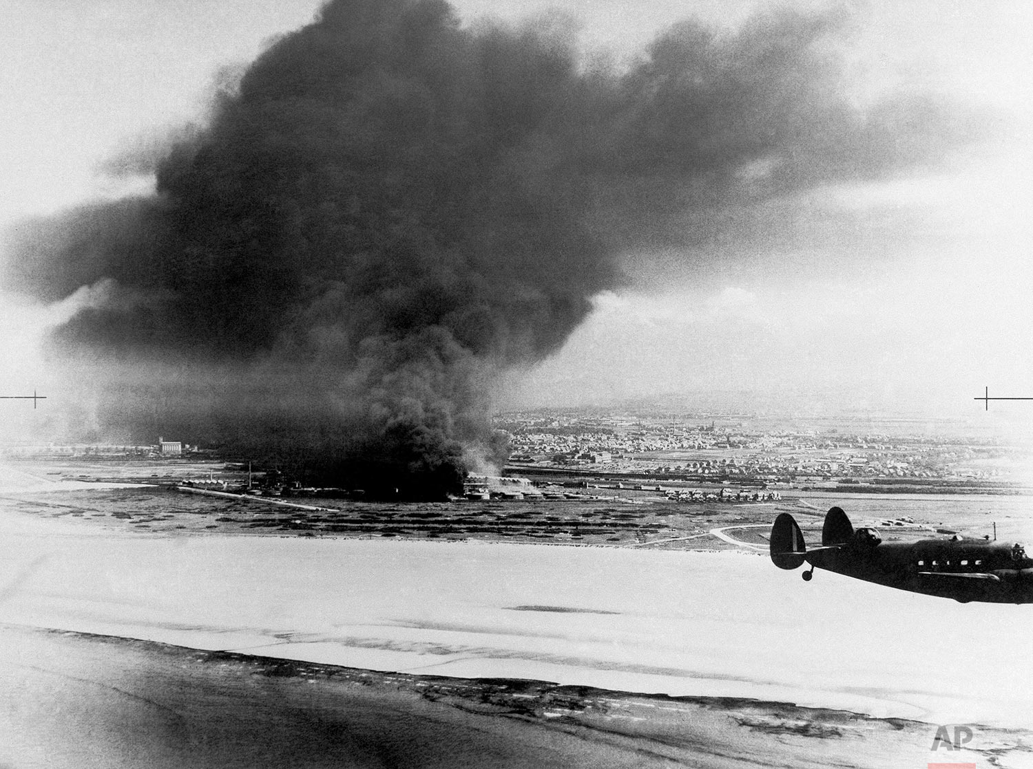 Dunkirk from the shore showing two burning oil tanks with Lockheed Hudson coastal command patrol plane in foreground on June 10, 1940 in France. (AP Photo)