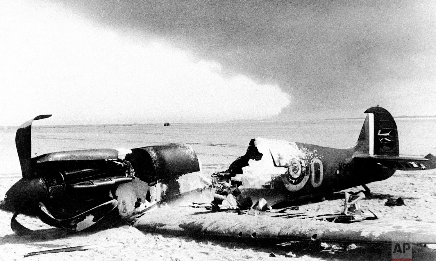 A British Spitfire fighter lays with its cockpit blasted out, after it crashed to the beach at Dunkirk, France on June 6, 1940, the last stand port of the Allied forces which fled from Flanders. Smoke from burning Dunkirk may be seen in the background. (AP Photo)