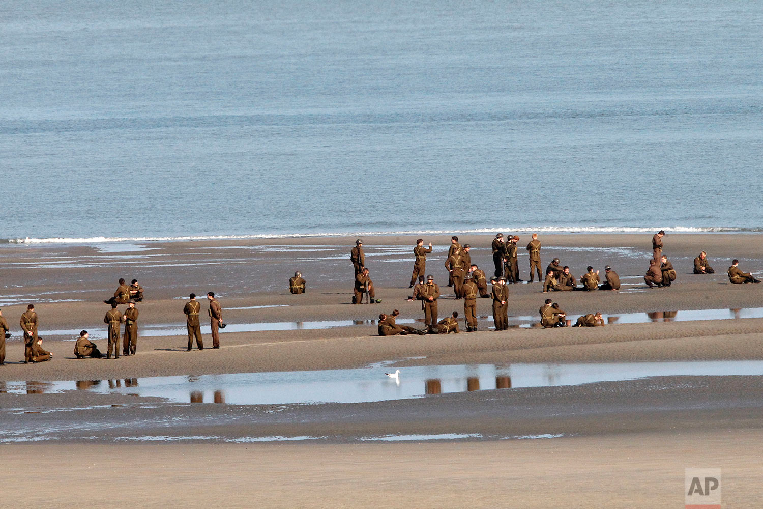 """Actors wait on the beach before filming a scene for the film, """"Dunkirk,"""" in Dunkirk, northern France, Thursday, May 26, 2016. The film, directed by Christopher Nolan, tells the story of the Dunkirk evacuation, which took place at the beginning of World War II. (AP Photo/Michel Spingler)"""