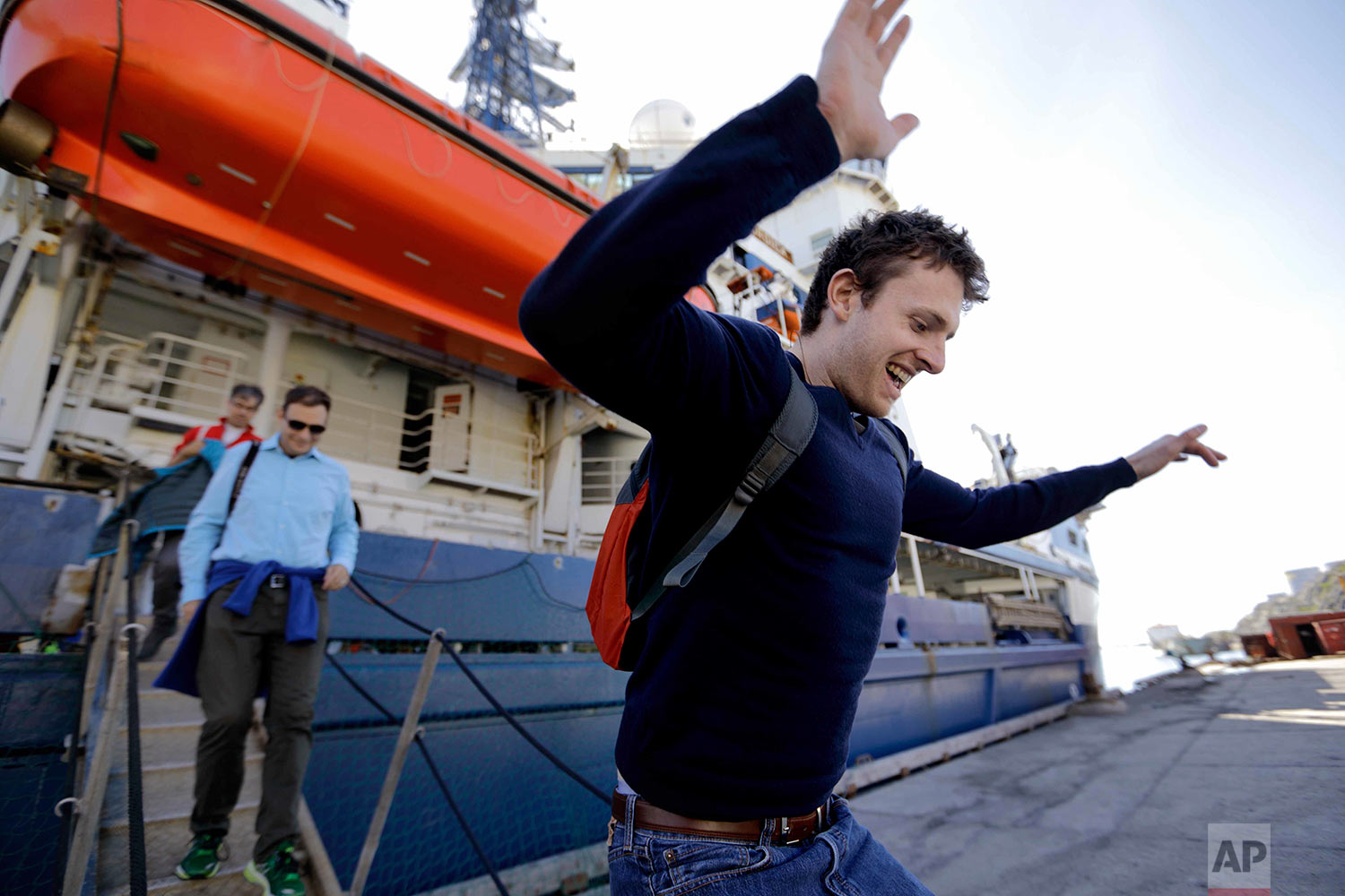 Researcher Scott Joblin jumps onto land for the first time since setting sail aboard the Finnish icebreaker MSV Nordica as it arrives into Nuuk, Greenland, after traversing the Northwest Passage through the Canadian Arctic Archipelago, Saturday, July 29, 2017. After 24 days at sea and a journey spanning more than 10,000 kilometers (6,214 miles), the MSV Nordica has set a new record for the earliest transit of the fabled Northwest Passage. The once-forbidding route through the Arctic, linking the Pacific and the Atlantic oceans, has been opening up sooner and for a longer period each summer due to climate change. (AP Photo/David Goldman)