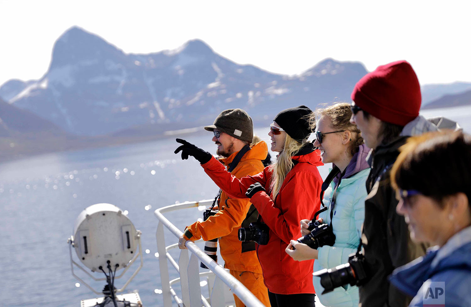 Tiina Jaaskelainen, second from left, and fellow researchers look out from the Finnish icebreaker MSV Nordica as it arrives into Nuuk, Greenland, after traversing the Northwest Passage through the Canadian Arctic Archipelago, Saturday, July 29, 2017. After 24 days at sea and a journey spanning more than 10,000 kilometers (6,214 miles), the MSV Nordica has set a new record for the earliest transit of the fabled Northwest Passage. The once-forbidding route through the Arctic, linking the Pacific and the Atlantic oceans, has been opening up sooner and for a longer period each summer due to climate change. (AP Photo/David Goldman)