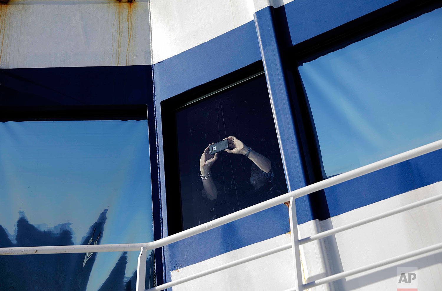 """Canadian ice navigator, David """"Duke"""" Snider takes a photo from the bridge as the Finnish icebreaker MSV Nordica arrives into Nuuk, Greenland, after traversing the Northwest Passage through the Canadian Arctic Archipelago, Saturday, July 29, 2017. After 24 days at sea and a journey spanning more than 10,000 kilometers (6,214 miles), the MSV Nordica has set a new record for the earliest transit of the fabled Northwest Passage. The once-forbidding route through the Arctic, linking the Pacific and the Atlantic oceans, has been opening up sooner and for a longer period each summer due to climate change. (AP Photo/David Goldman)"""