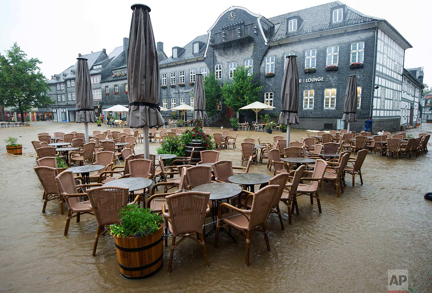 Tables and chairs of a cafe sit empty in the flooded Marktplatz square in Goslar, Germany, Wednesday, July 26, 2017. (Swen Pfoertner/dpa via AP)