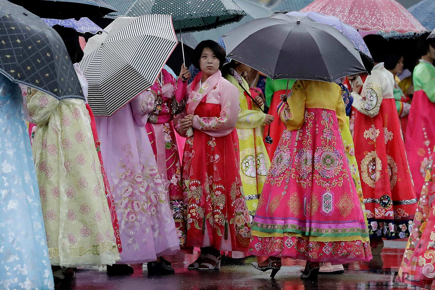 University students wearing traditional Korean dresses wait in the rain for the start of a group dance on Thursday, July 27, 2017, in Pyongyang, North Korea as part of celebrations for the 64th anniversary of the armistice that ended the Korean War. (AP Photo/Wong Maye-E)