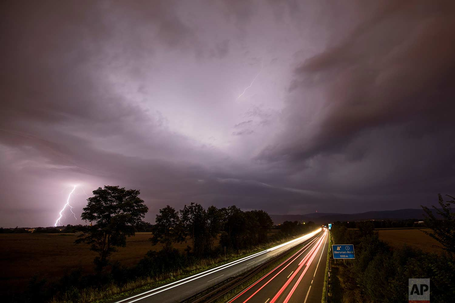 In this photo made with a long exposure, cars drive by as lightning strikes during thunderstorms in Oberursel, Germany, near Frankfurt on Saturday, July 22, 2017. (Jan Eifert/dpa via AP)