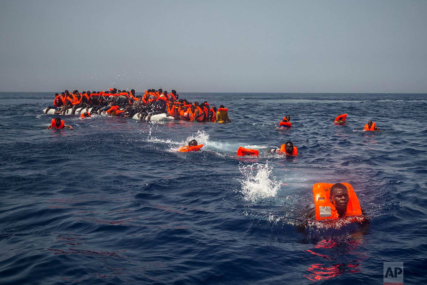 African migrants try to reach a Spanish NGO Proactiva Open Arms rescue ship after falling from a punctured rubber boat in the Mediterranean Sea, about 12 miles north of Sabratha, Libya on Sunday, July 23, 2017. (AP Photo/Santi Palacios)