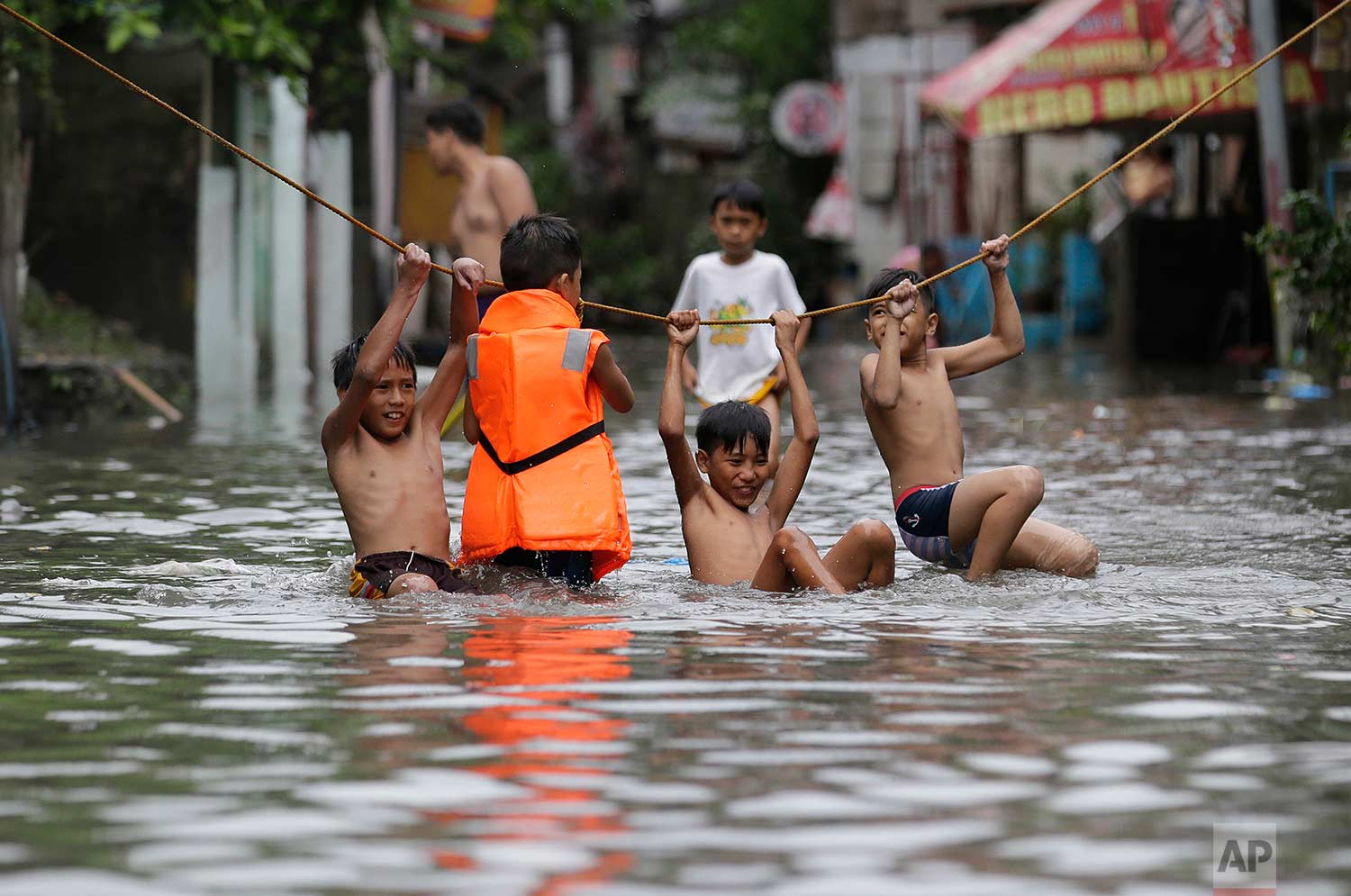Boys play outside their flooded homes after heavy rains from tropical storm Gorio flooded parts of metropolitan Manila, Philippines on Thursday, July 27, 2017.  (AP Photo/Aaron Favila)