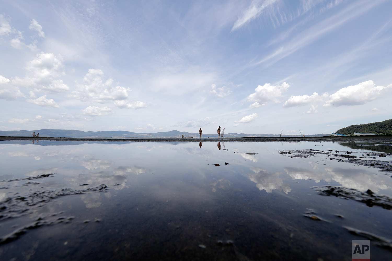 People walk along the shore of Lake Bracciano, about 35 kilometers (22 miles) northwest of Rome, Thursday, July 27, 2017. (AP Photo/Andrew Medichini)