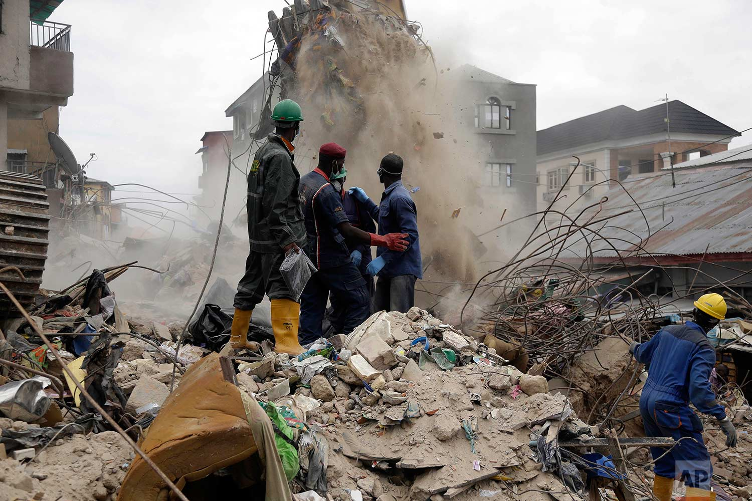 Rescue workers looking for survivors watch as debris falls from a collapsed building in a densely populated neighborhood in Lagos, Nigeria, Wednesday, July 26, 2017. (AP Photo/Sunday Alamba)