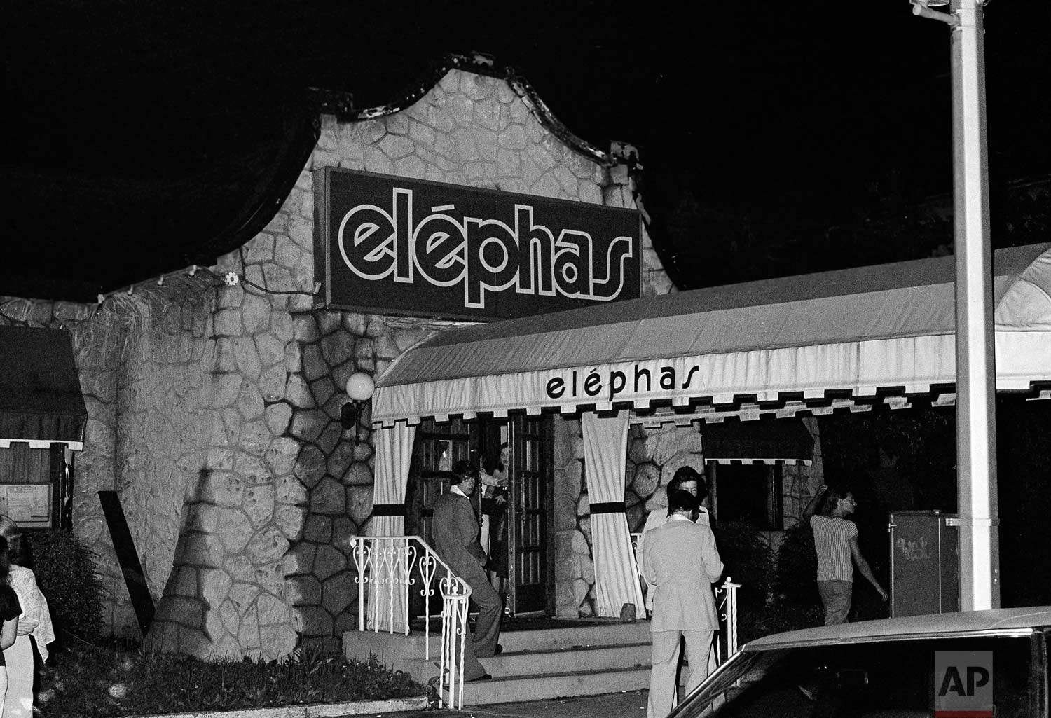 "People stand outside of the Elephas nightclub in the early morning hours of June 26, 1977, in the Bayside section of the Queens borough of New York, where a young couple parked near the club were shot by the "".44 Caliber Killer"" also known as the ""Son of Sam"".  (AP Photo)"