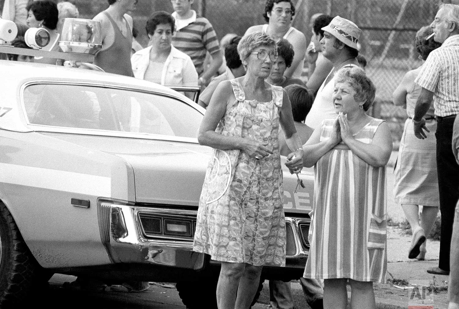 "Residents of Bensonhurst section of Brooklyn and police officers stand near the scene of the shooting by "".44 Caliber Killer"" at Shore Parkway and Bay 16 in New York, July 31, 1977. (AP Photo)"