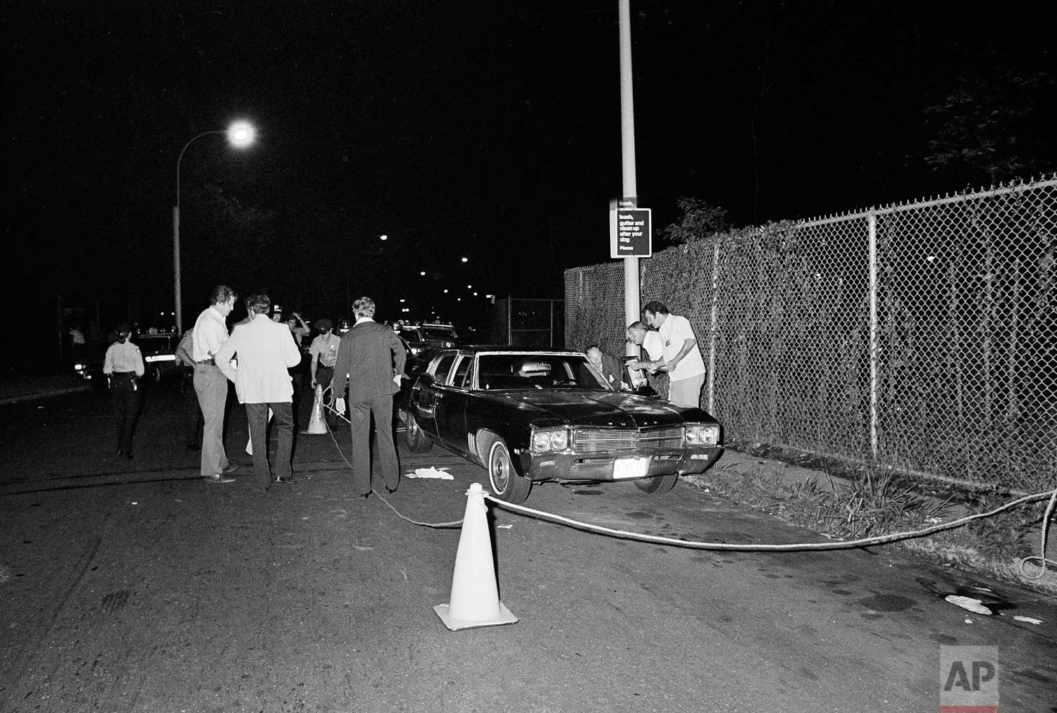 "Police rope off the area around a car as they search for evidence in the early morning hours of July 31, 1977, after a gunman shot a young couple parked in a secluded lovers' lane in the Gravesend section of the Brooklyn borough of New York. Police believe it was another ""Son of Sam"" shooting. (AP Photo)"
