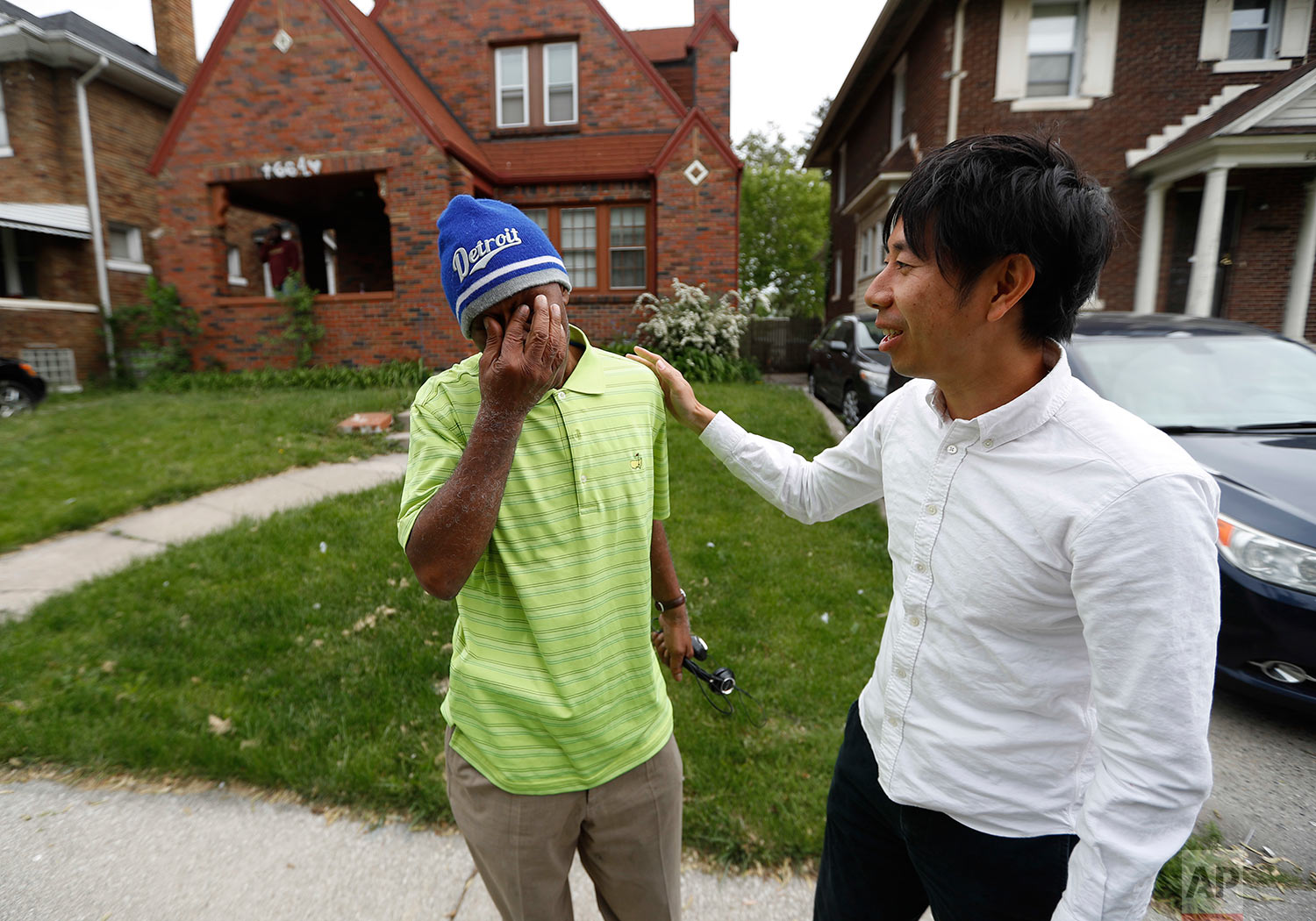 John Hall, left, is overcome saying goodbye to Motoki Taniguchi, Reentry Coordinator with the Michigan State Appellate Defender Office in Detroit, Friday, May 19, 2017.  (AP Photo/Paul Sancya)