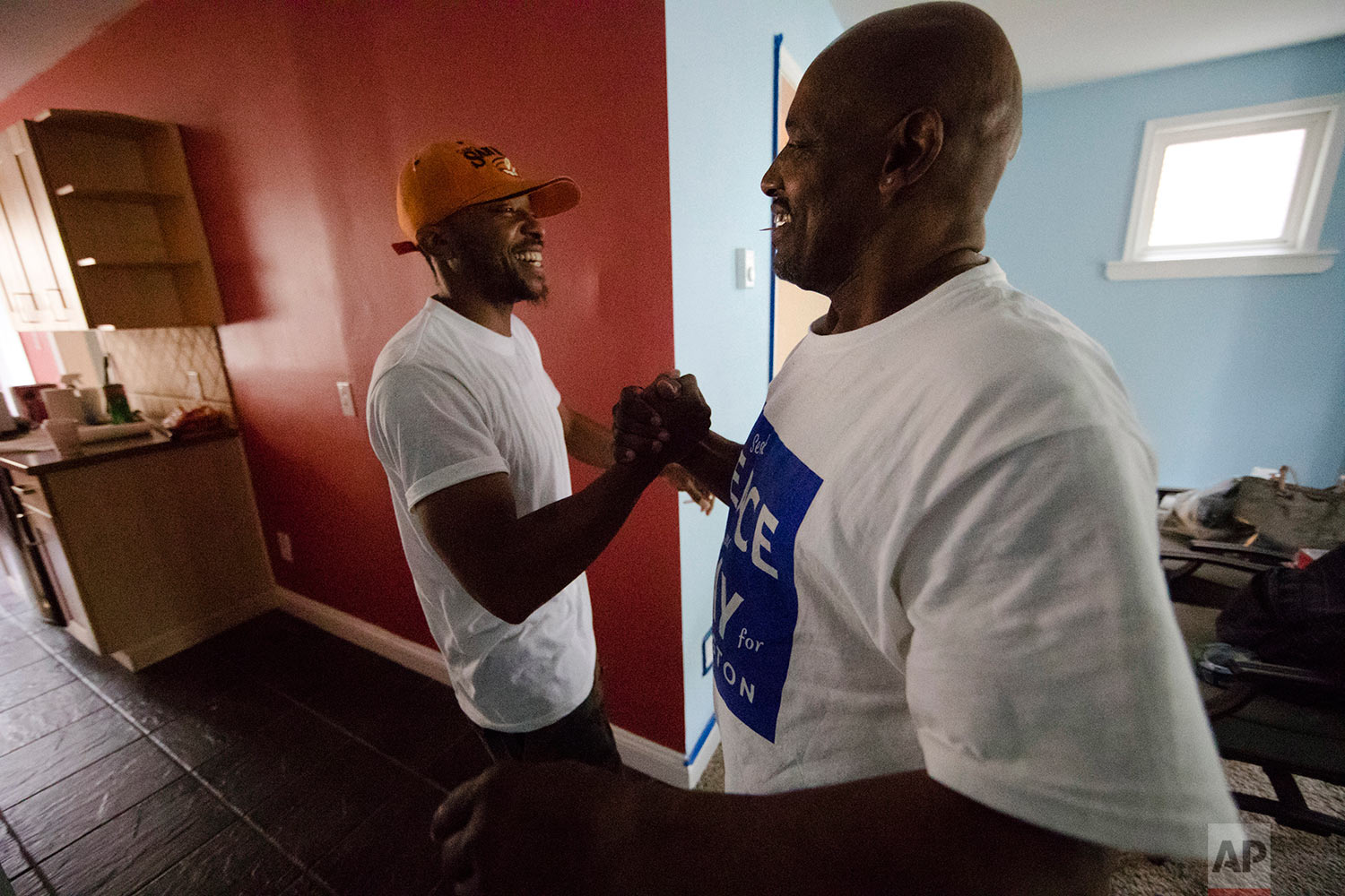 Earl Rice Jr., right, greets Justin Coleman as he arrives to help family members paint a newly-bought home in Wilmington, Del., Saturday, May 20, 2017. (AP Photo/Matt Rourke)