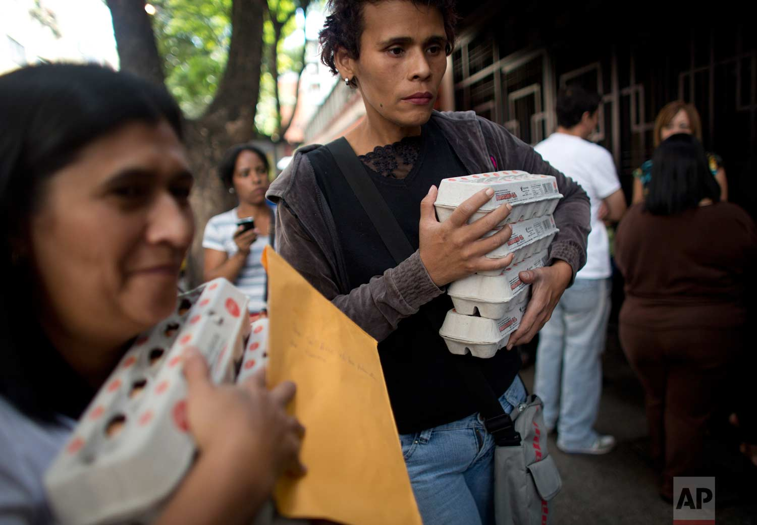People carry boxes of eggs after buying them at government regulated prices in Caracas, Venezuela, during an egg shortage. (AP Photo/Ariana Cubillos)