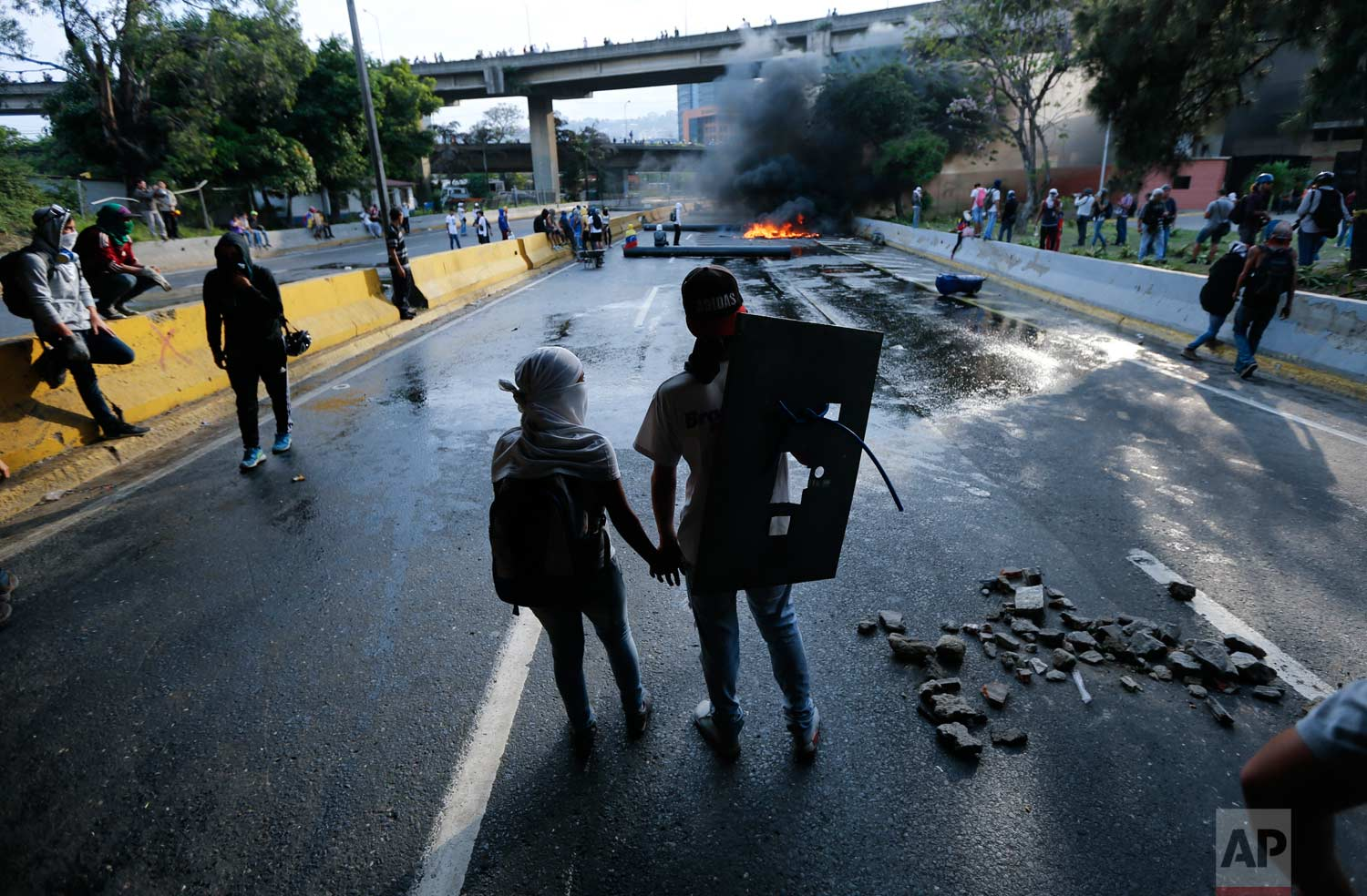 A couple holds hands at a road block set by anti-government protesters in Caracas, Venezuela. Protesters shut down the capital city's main highway to express their disgust with the administration of President Nicolas Maduro. (AP Photo/Ariana Cubillos)