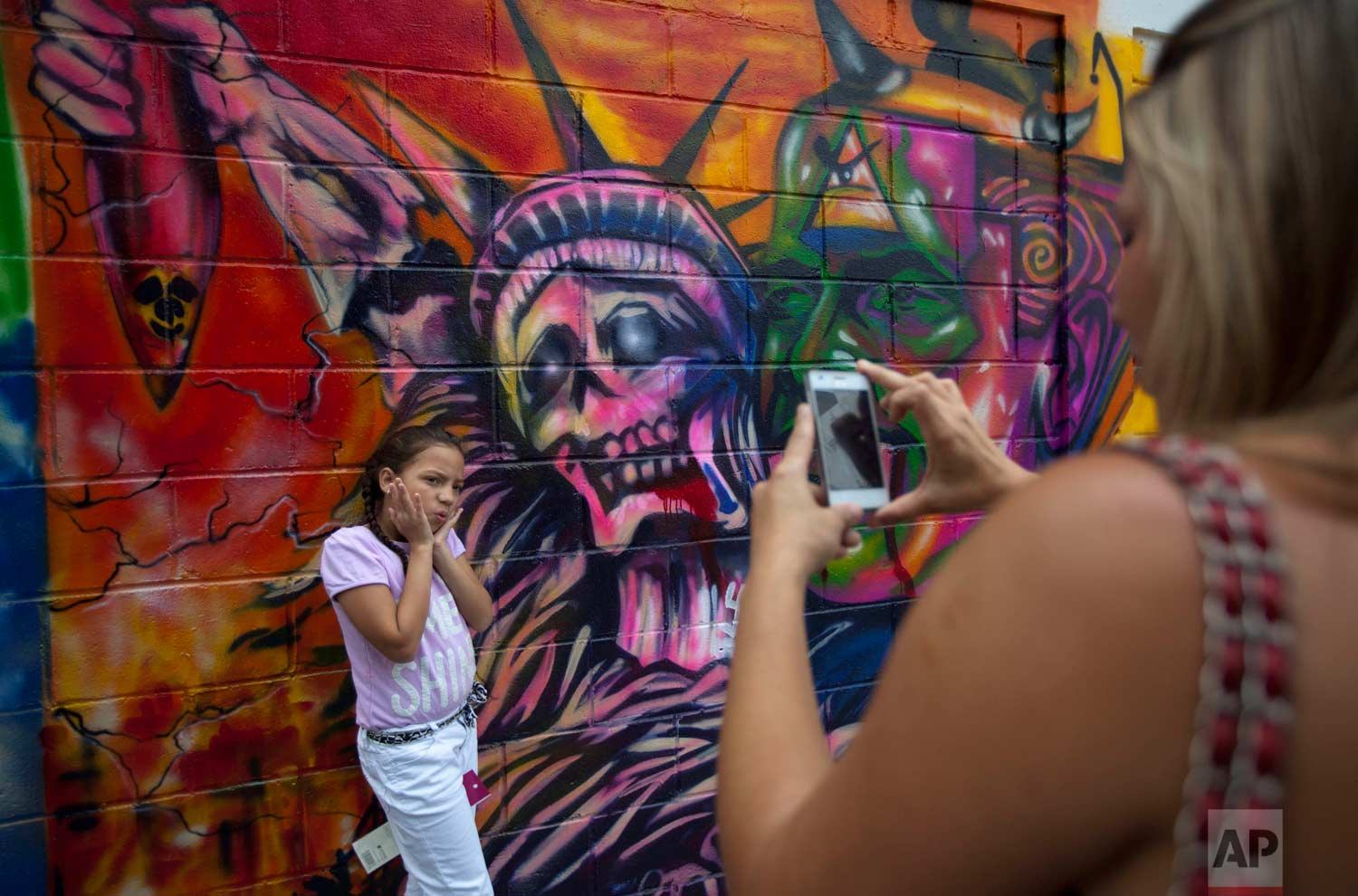 In this March 19, 2015 photo, a girl poses for a picture in front of a mural depicting the statue of liberty as death, at Bolivar square in Caracas, Venezuela. (AP Photo/Ariana Cubillos)