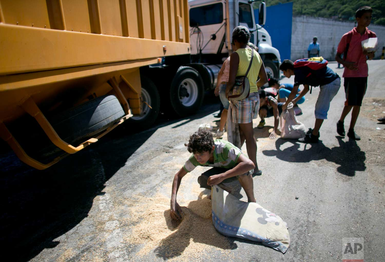 In this Nov. 14, 2016 photo, a boy uses his pillowcase as a bag to collect rice from the pavement that shook loose from a food cargo truck waiting to enter the port in Puerto Cabello, Venezuela, the port that handles the majority of Venezuela's food imports. As millions of Venezuelans go hungry this year, food trafficking has become one of the most lucrative businesses in the country. (AP Photo/Ariana Cubillos)