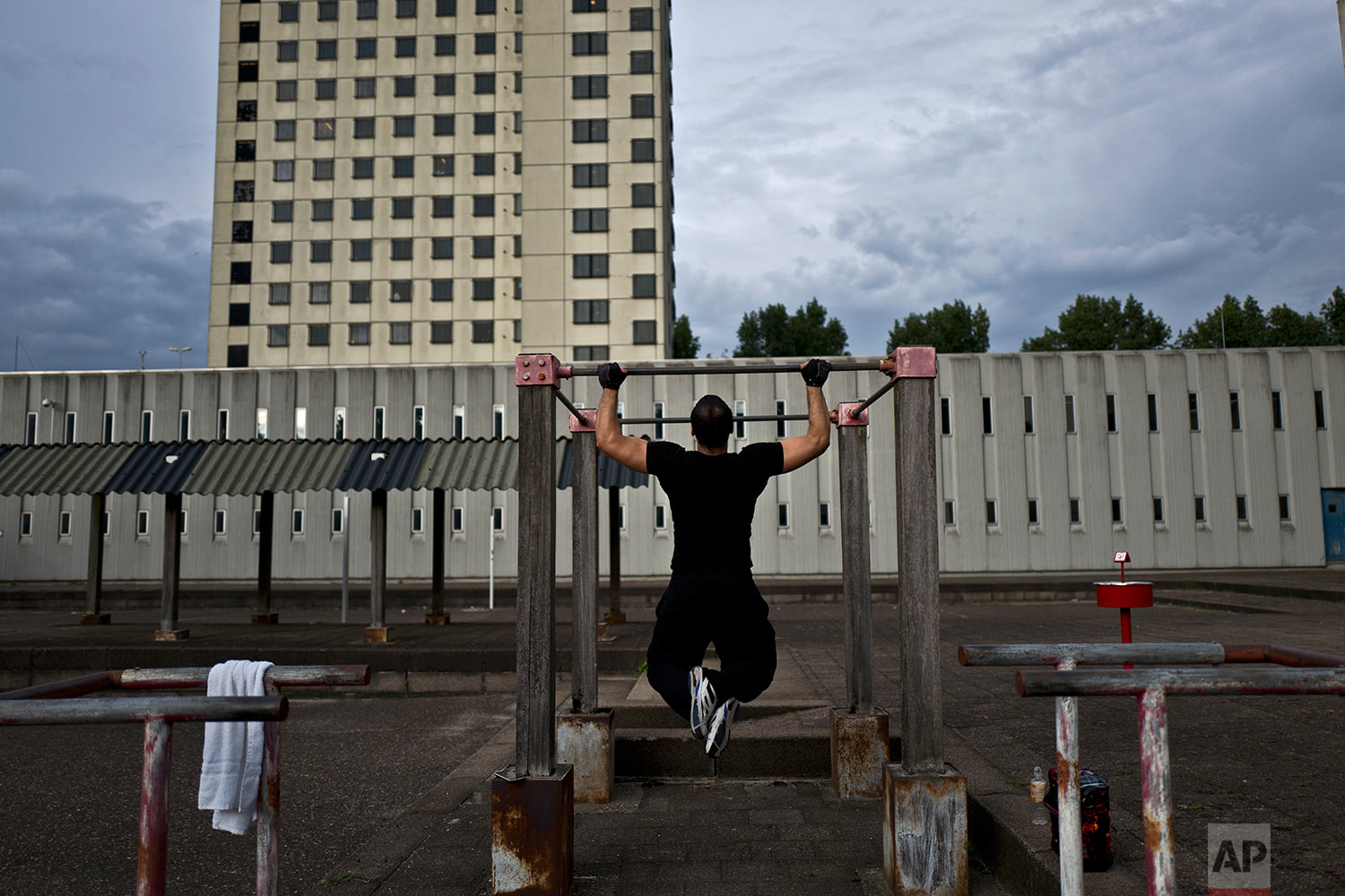In this Saturday, July 22, 2017 photo, Afghan refugee Zafar Sahil, 22, exercises in a yard at the former prison of Bijlmerbajes in Amsterdam, Netherlands. (AP Photo/Muhammed Muheisen)