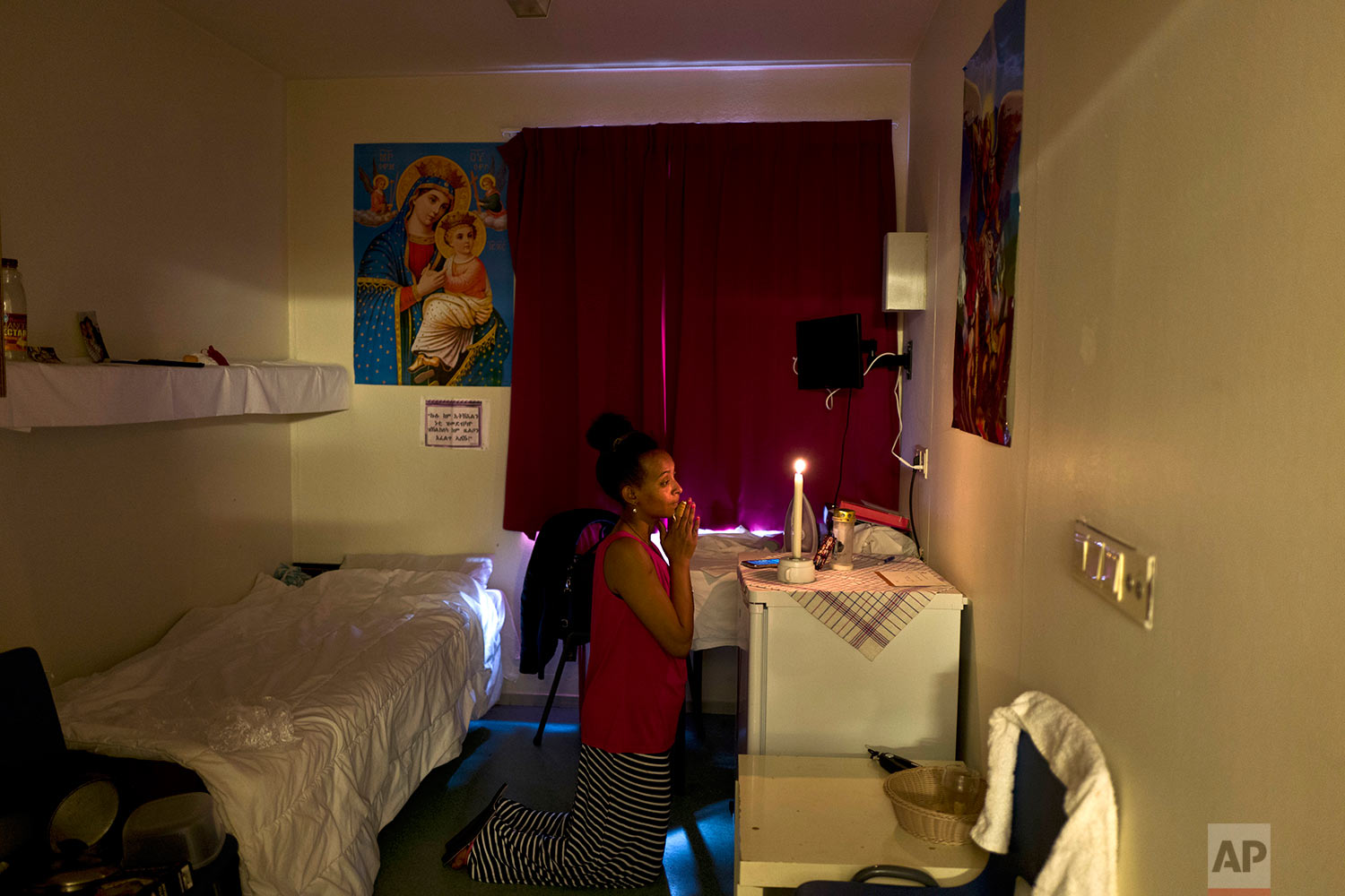 In this Monday, June 26, 2017 photo, Meza Negadtu, 29, a migrant from Eritrea, prays inside her room at the former prison of Bijlmerbajes, in Amsterdam, Netherlands. (AP Photo/Muhammed Muheisen)